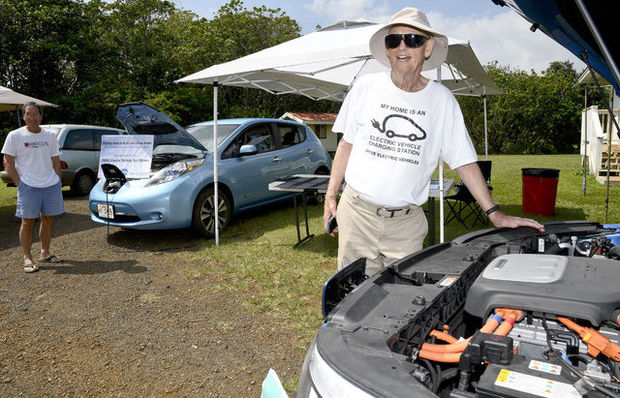 Al Pugsley, visiting from Kansas City, checks out the engine of a Kia EV while David Lee watches the Nissan Leaf Saturday during the Kauai Community Market at Kauai Community College.