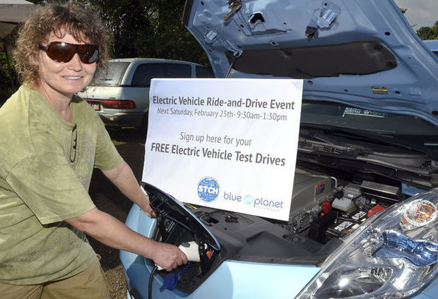 Sonia Kass plugs in the power cord to the Nissan Leaf Saturday during the Kauai Community Market at Kauai Community College.